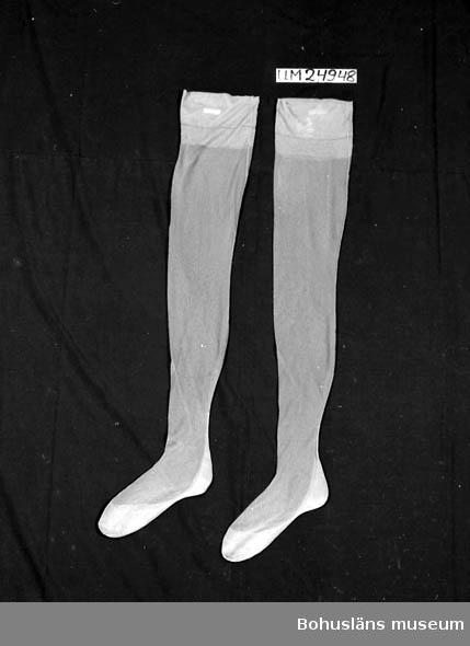 """Grå-beige. Med söm och förstärkt fot. På ena strumpans överkant tryckt text:""""Esprit MADE OF DIAMANTNYLON 51GAUGE 30 DEN FIRST QUALITY"""". Enligt givaren kallas materialet för glasnylon, en tidig efterföljare till silkesstrumporna."""