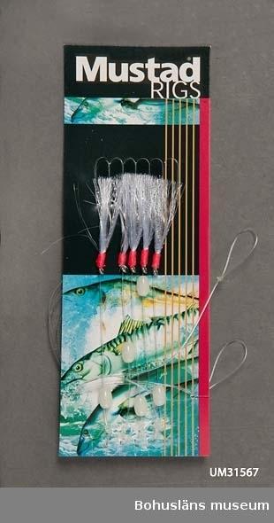 """Två förpackningar med vardera fem häcklor, metallkrok med hulling och tafs av nylonborst med skarpt orange lindning fästad i  nylonlina med litet ovalt plastflöte, lyskula. Originalförpackning, plastpåse med pappförpackning märkt Mustad RIGS med foto på hoppande makrill och på baksidan reklamtext för Mustad """"Selling Hook Brand SINCE 1877. These rigs are phenomenally effective for cod and flatfish species."""" Mustad Terminal Tackle, Phillipines. Hooks made by Mustad & Sons A.S., Norway. På pappen sitter fem häcklor fästade. På butikens medföljande packsedel kallas redskapet häckla. Mer information om  företaget på Internet 2011: www.mustad.no  Inköpt till föremålssamlingarna i samband med utställningen Fri och ledig!? sommaren 2011. Text till utställningen Fri och Ledig!?: Sverige har fina möjligheter till fritidsfiske. 90 000 sjöar, 100 000 vattendrag och en lång kust. Det behöver inte vara dyrt. Men vi satsar gärna. Särskilt männen: 1,5 miljarder kronor läggs på båt och utrustning varje år. Fisketurism är en guldkantad nisch för näringslivet. Allt från hummersafari på Västkusten till exklusivt fiske i avlägsna fjällsjöar. Det finns en stor utländsk fisketurism. Utomlands är många vatten privatägda. Alla har rätt att fiska med handredskap vid kusten och i de fem stora sjöarna Vänern, Vättern, Mälaren, Hjälmaren och Storsjön. Man får meta, spinnfiska, pilka och pimpla och fiska med lina som har max 10 krokar. Till andra vatten kan man köpa fiskekort."""