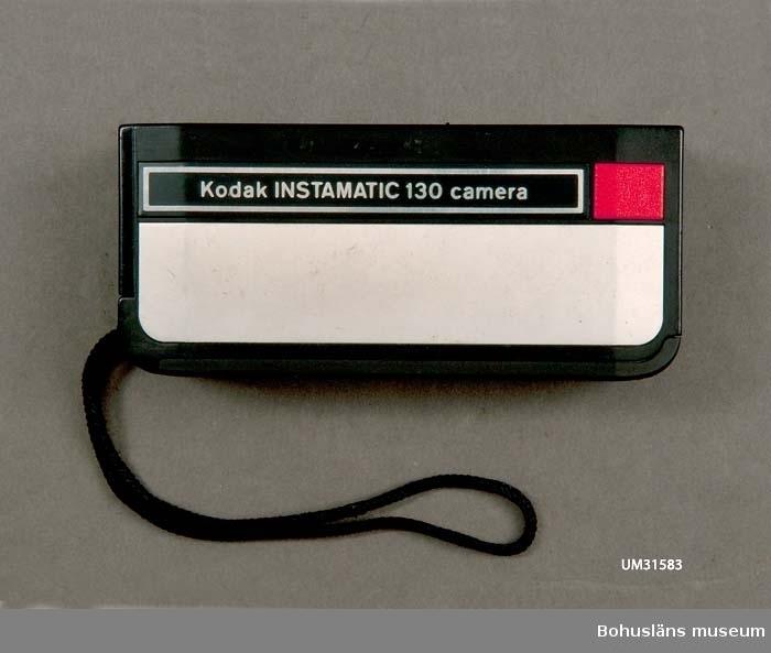 Rektangulär pocketkamera i svart plast med handledssnöre. Röd avtryckarknapp. Modell: Kodak INSTAMATIC 130 camera. Ingjuten text: MADE IN GERMANY och märkt  med Kodaks varumärke i metall Ena långsidan öppningsbar föratt sätta i och ta ut filmrullen. Detta var givarens första egna kamera.