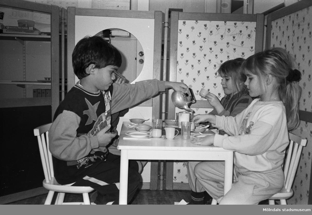 """Fyra barn sitter och """"fikar"""" vid ett barnbord. De har små kaffekoppar och fat på bordet. En pojke häller upp kaffe från en liten kittel av metall. I bakgrunden ser man en utvecklad avskärmningsdel som är klädd i olikfärgade tyger. Katrinebergs daghem, 1992."""