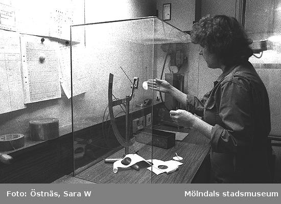 En kvinna i pappersfabriken mäter vikten på de olika skikten på den färdigtillverkade kartongen, 1980-tal. Bilden ingår i en serie från produktion och interiör på pappersindustrin Papyrus.