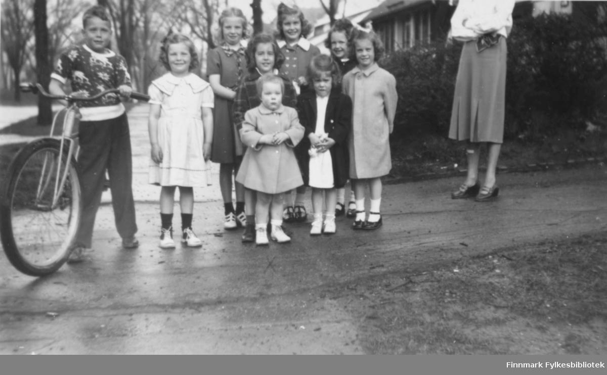 En gruppe av 9 barn  mellom 2 og 8 år fotografert på en våt gate i Michigan, Usa. Barna (minst tre av dem) er etterkommere av finsk/norske emigranter fra Vadsø. Gutten med sykkelen heter Sandy og er 7 år gammel, søsteren hannes står ved sidan av han kledd i en lys kjole, hun er 5 år, og den meinste av søskene står fremst på bildet: en to åring jente med kjoleaktig jakke på seg. De andre ungene er ikke navngitt..   Moren til de tre barna står lengst til høyre men hodet hennes er ikke blitt med på bildet. Navne hennes er heller ikke kjent.