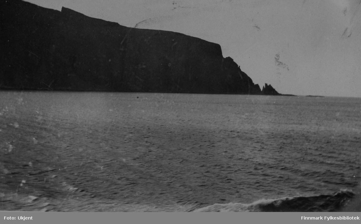 Bildet tatt i Finnkirke, Kjøllefjord. Mer om bildet er uvist. På bildet kan man se hav og fjell. Helt i høyre hjørne kan man se en bølge.