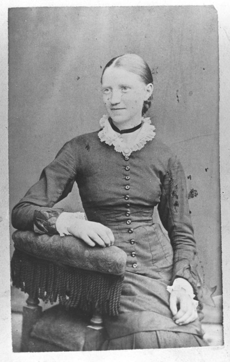 Et visitkortportrett av en ung kvinne, Tora Linseth. Hun er kledd i kjole med en lang rad av knapper foran. Hun sitter på en lenestol handen på ryggstøen og smiler pent
