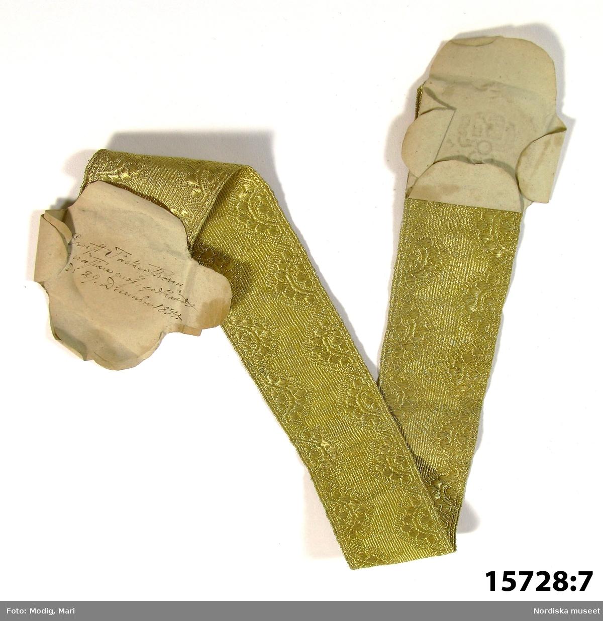 """Huvudliggaren: """"Låda m.m., som tillh. snörmakarämbetet i Stockholm. Med 3 nycklar, 43 st mästerprof i guld eller silfver, 27 st. mästerprof i silke och guld. Handlingar, som tillh. samma ämbete se 15.592. a) Låda. b) Sigillstamp, se ill. bil. (inga ren...[?] skrifna, se ill. bil med blyerts, osäkert om det är b eller c.). c) Sigillstamp. d) Pung. e) Skärp fr 1840-talet, nu nyl. afl. snörmakare Bretzners mästerprof. f) Pergamentsbref med vidhängande vaxsigill. g) Pergamentsbref med vidhängande vaxsigill. h) Pergamentsbref med vidhängande vaxsigill i kapslar. i) Pergamentsbref med vidhängande vaxsigill i kapslar. j) Pergamentsbref med vidhängande vaxsigill i kapslar. k) Pergamentsbref med vidhängande vaxsigill i kapslar. l) Pergamentsbref med vidhängande vaxsigill i kapslar. m) Pergamentsbref med vidhängande vaxsigill i kapslar. n) Pergamentsbref med vidhängande vaxsigill i kapslar. o) Pergamentsbref med vidhängande vaxsigill i kapslar. p) Pergamentsbref med vidhängande vaxsigill i kapslar. q) Pergamentsbref med vidhängande vaxsigill i kapslar. r) Pergamentsbref med vidhängande vaxsigill i kapslar. s) Sparbössa. t) Handlingar. u) Handlingar. v) Nyckel, järn, L 12,4 cm. Trepassformat grepp. w) Nyckel, järn, L 10,1 cm. Trepassformat grepp. x) Nyckel, järn. L 2,2 cm. G. af f.d. snörmakar.ämb. i Stockh. gm snörmak. C. E. Hähnel. 30/1 1877."""""""
