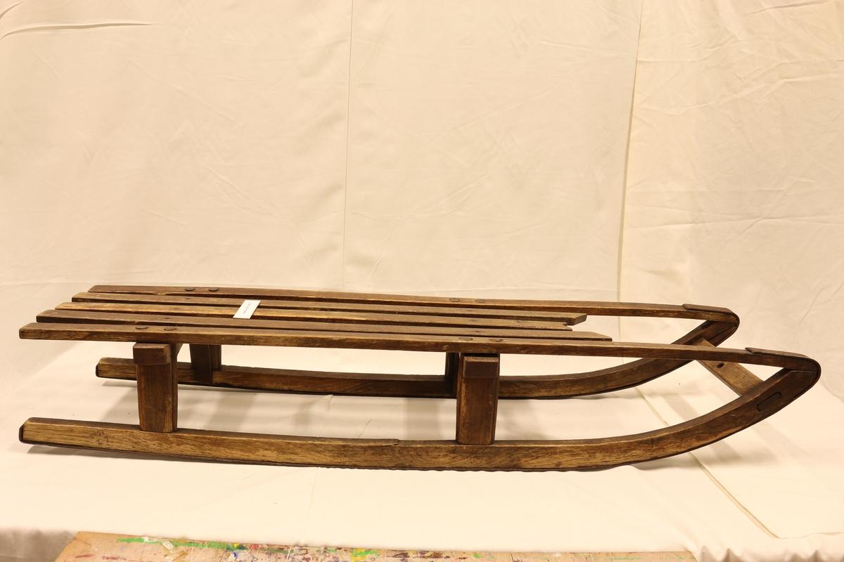 Laget av tre og har jernbeslag på meiene. Brun tre lakk farge. Jernforsterkning fra meiene til toppen. Setet på kjelken laget av spiler.