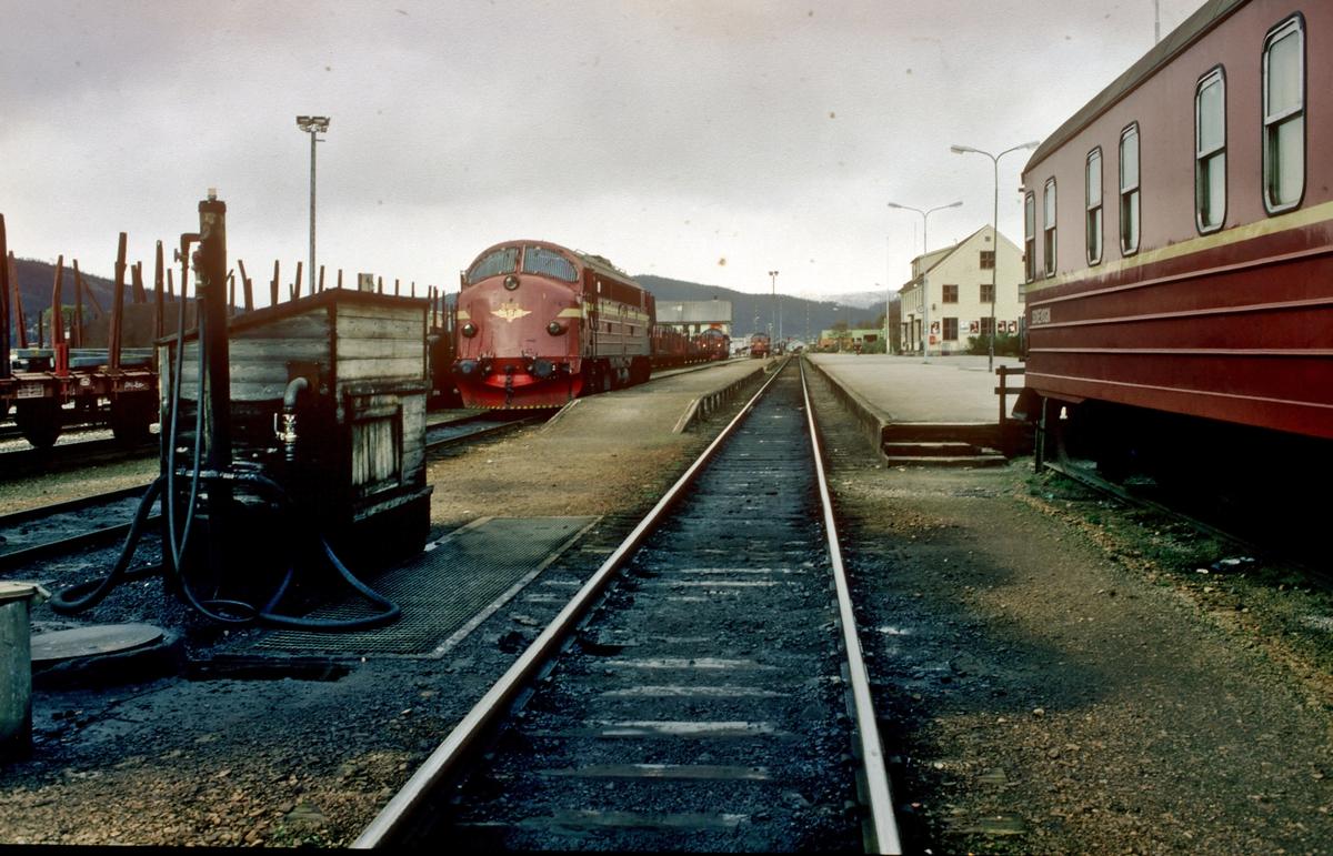 Mo i Rana stasjon våren 1983. Til høyre står sovevogna som har blitt skiftet ut av nattoget. Til venstre ser vi fyllingsanlegget for diesel. Noen lokomotiver av type Di 3 står rundt på stasjonsområdet.
