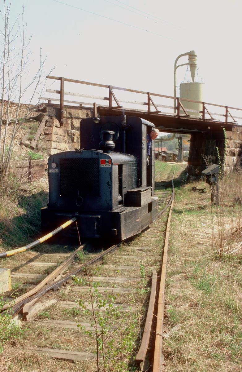 Saugbrugsforeningens jernbane i Halden (Norske Skog Saugbugs). Diesellokomotiv på sagbrukets område med tog på vei gjennom undergangen under Østfoldbanen. Industrilokomotiv, Deutz.