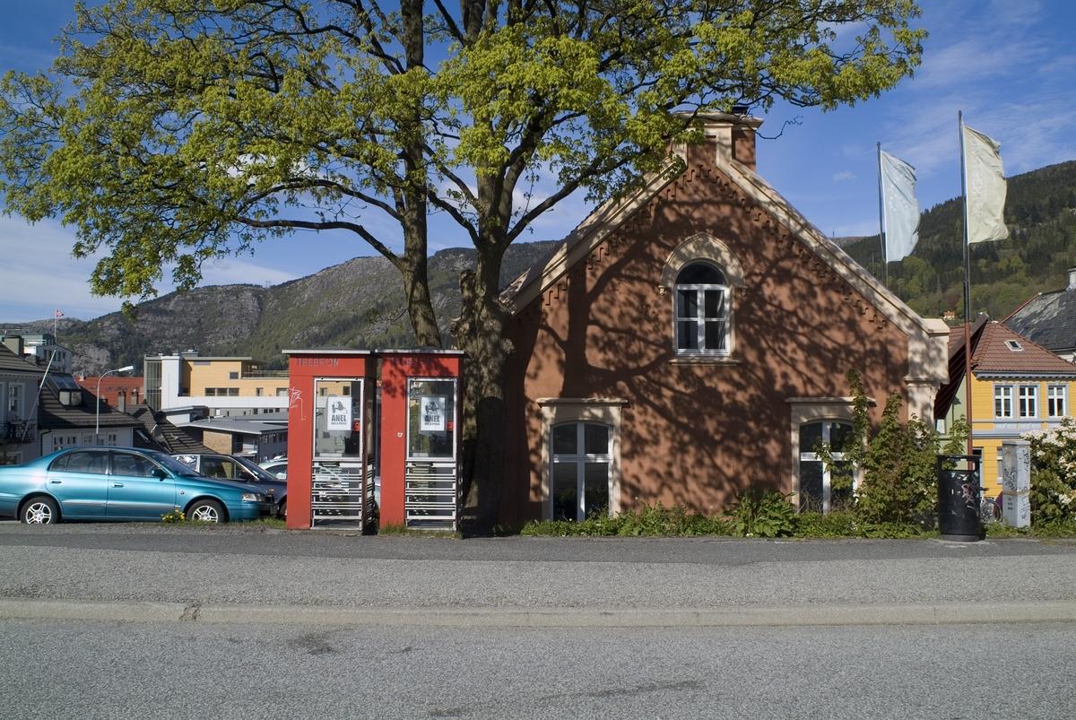 Denne telefonkiosken står ved Klosteret 17 i Bergen, og er en av 100 vernede telefonkiosker i Norge. De røde telefonkioskene ble laget av hovedverkstedet til Telenor (Telegrafverket, Televerket). Målene er så å si uforandret.  Vi har dessverre ikke hatt kapasitet til å gjøre grundige mål av hver enkelt kiosk som er vernet.  Blant annet er vekten og høyden på døra endret fra tegningene til hovedverkstedet fra 1933. Målene fra 1933 var: Høyde 2500 mm + sokkel på ca 70 mm Grunnflate 1000x1000 mm. Vekt 850 kg. Mange av oss har minner knyttet til den lille røde bygningen. Historien om telefonkiosken er på mange måter historien om oss.  Derfor ble 100 av de røde telefonkioskene rundt om i landet vernet i 1997. Dette er en av dem.