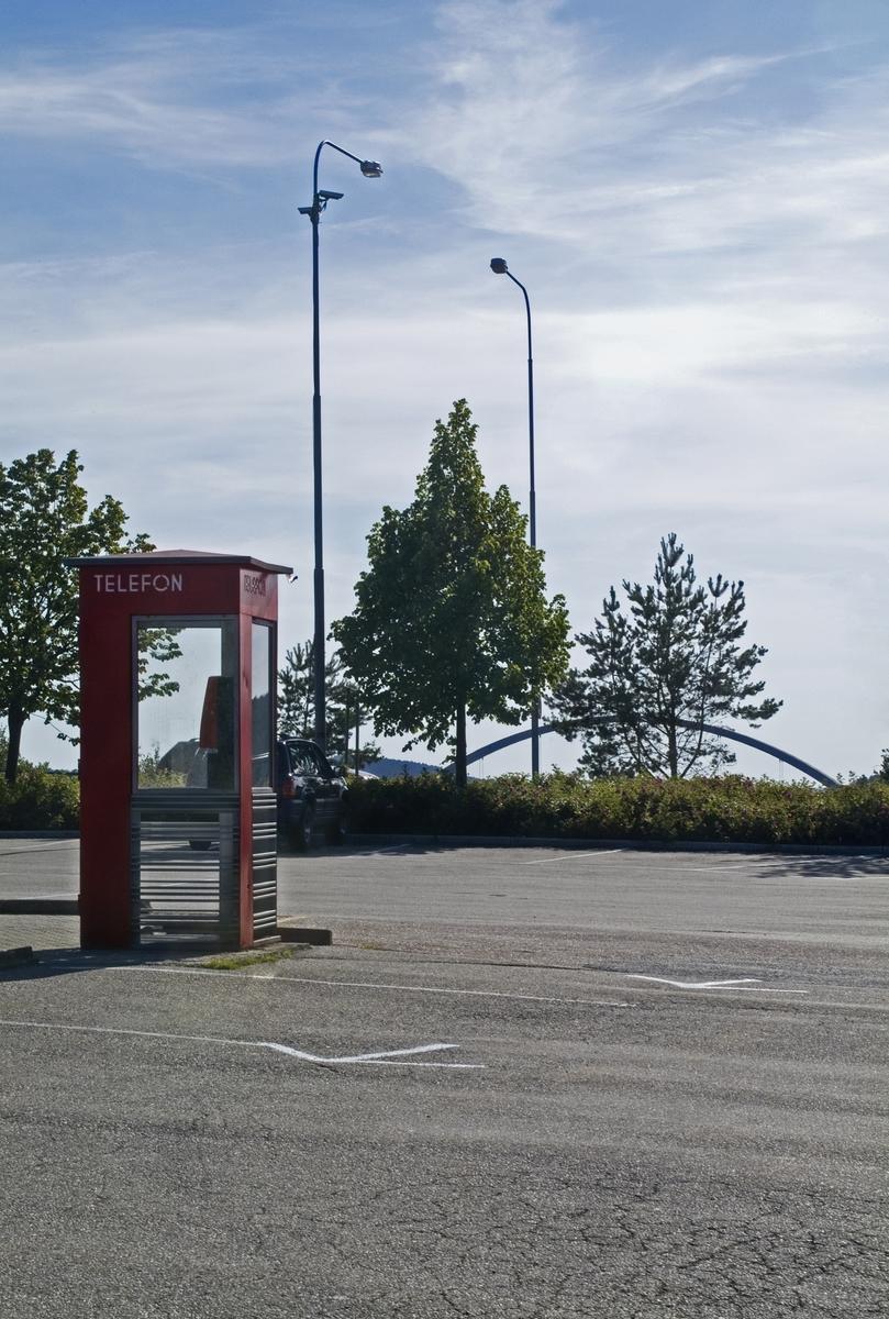 Denne telefonkiosken står ved Svinesund, og er en av de 100 vernede telefonkioskene i Norge. De røde telefonkioskene ble laget av hovedverkstedet til Telenor (Telegrafverket, Televerket). Målene er så å si uforandret.  Vi har dessverre ikke hatt kapasitet til å gjøre grundige mål av hver enkelt kiosk som er vernet.  Blant annet er vekten og høyden på døra endret fra tegningene til hovedverkstedet fra 1933. Målene fra 1933 var: Høyde 2500 mm + sokkel på ca 70 mm Grunnflate 1000x1000 mm. Vekt 850 kg. Mange av oss har minner knyttet til den lille røde bygningen. Historien om telefonkiosken er på mange måter historien om oss.  Derfor ble 100 av de røde telefonkioskene rundt om i landet vernet i 1997. Dette er en av dem.