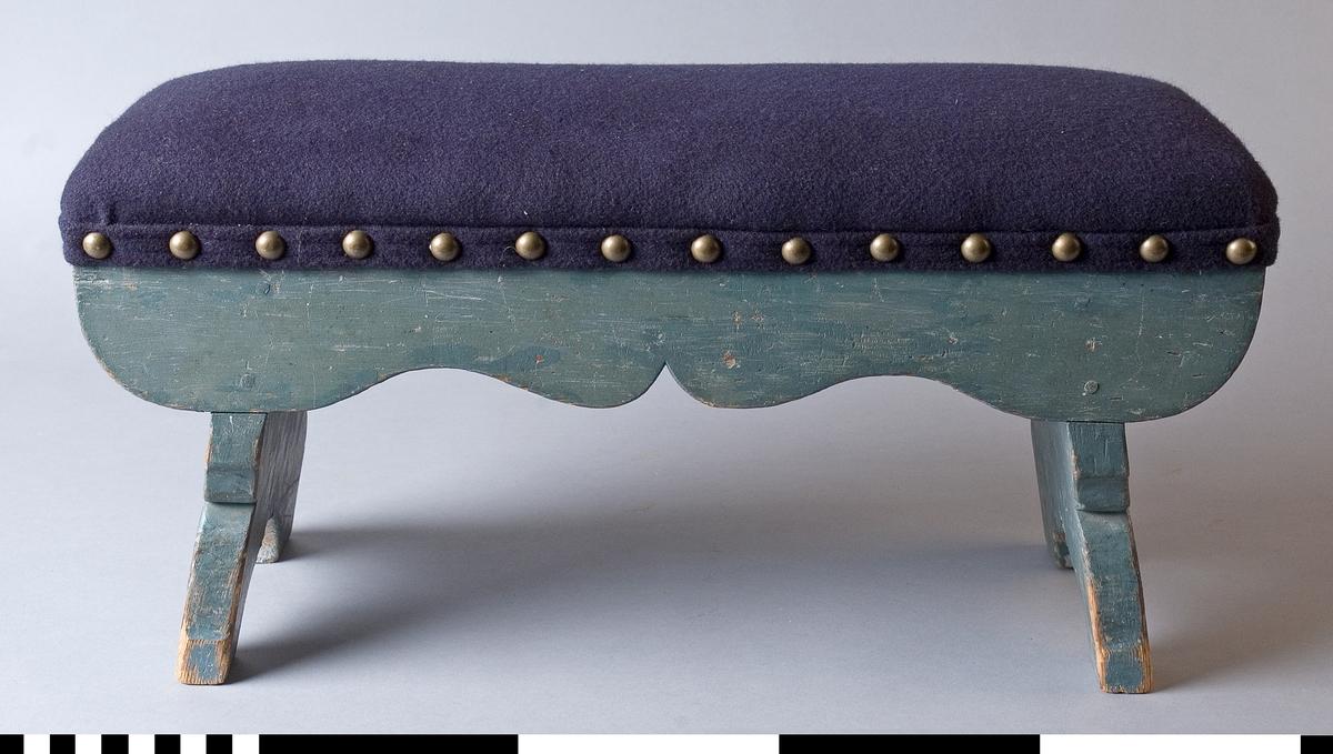 Pall tillverkad av trä. Delvis skulpterade gavlar, skulpterad frontlist. Målad i blågrönt, stoppad och klädd med blått ylletyg. Tännlikor.