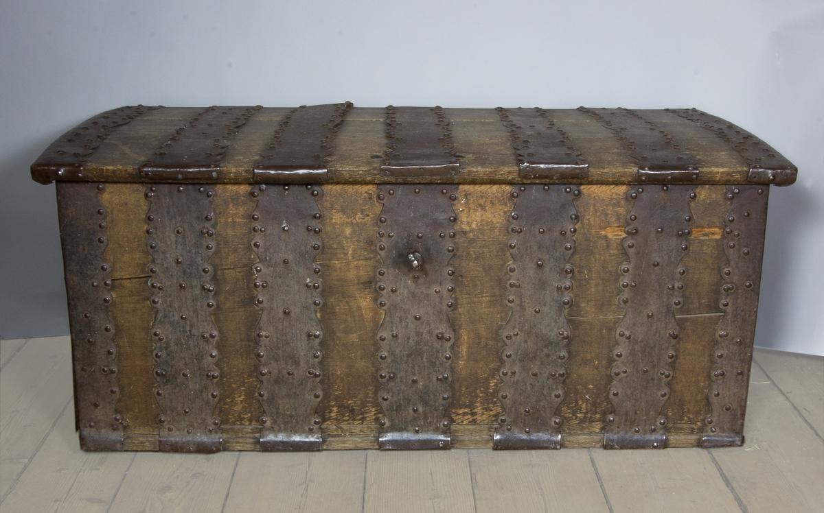 Kista, rektangulär med plant lock, något överskjutande, av ek med breda järnbeslag. Läddika och lönnlåda vid ena kortsidan. Nyckel.