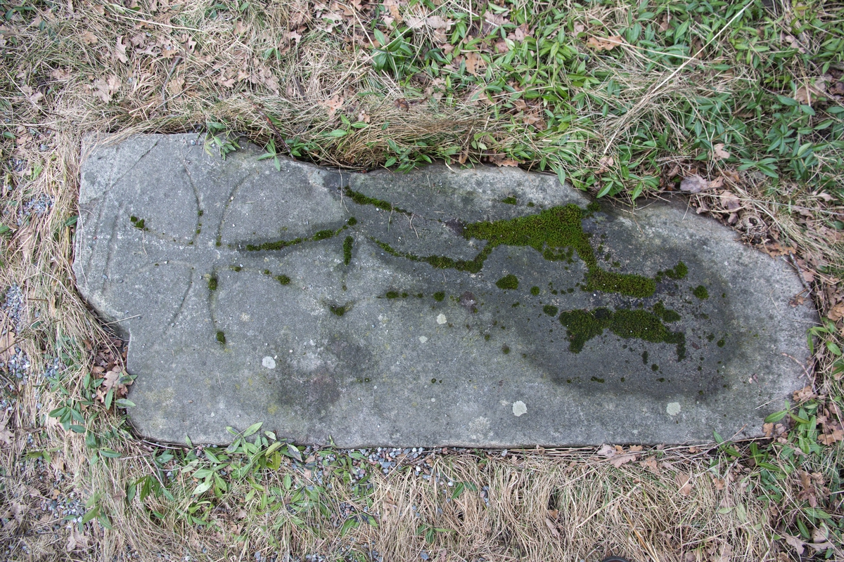 Gravsten, huggen av sten, avsedd att ligga horisontellt. Ovansidan med kors på trappstenformig fot. Av inskriften är endast knappt synliga spår kvar.