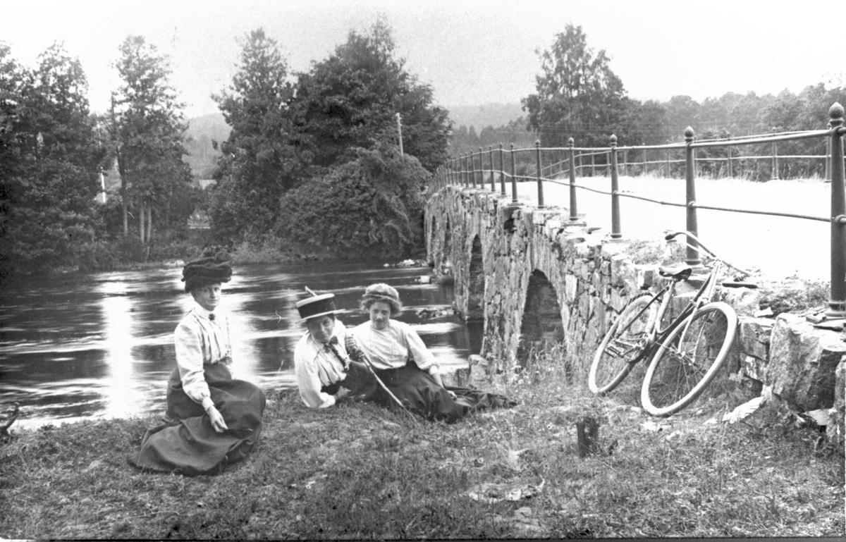 Kvinnor på cykeltur vilar i gröngräset vid vattnet.