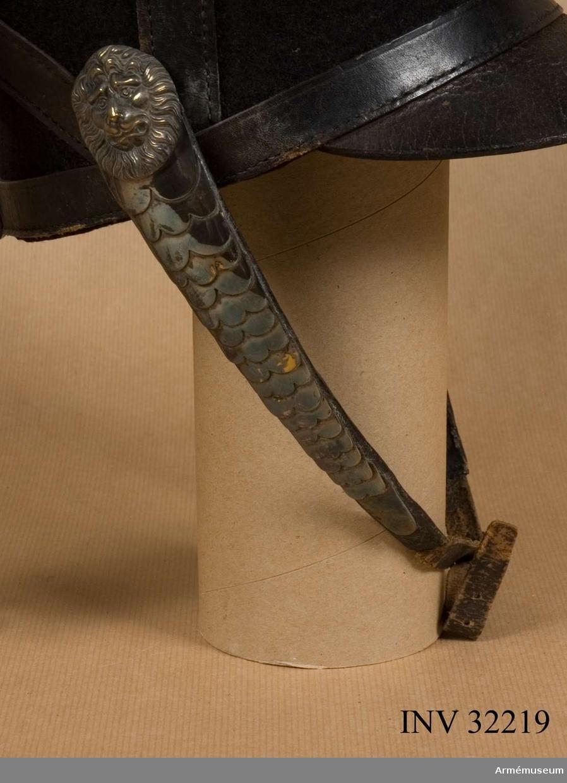 Grupp C I. Fjällband till tschakå. Ur uniform för manskap vid Livgardet till häst, 1814-20. Består av dolma, päls, spännhalsduk, byxor, knutskärp, tschakå med plym och kordong, pompong, vapenplåt, tjällband, knappar, sölja, kartusch med kartuschrem, sabelkoppel, sabeltaska med 3 remmar, sabel med balja, sabelhandrem, stövlar med sporrar, handskar. PUBL  AMV Meddelande XIX, s.112.
