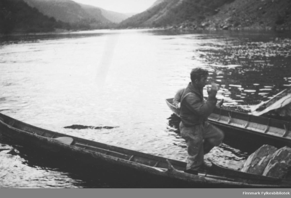 Altaelva. Vi ser en mann som balanserer i en elvebåt. Det ser ut som han holder på å ta overbalanse i det han prøver å gå i land? I bakgrunnen ser vi elvedalen