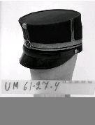 """Föremålet visas i basutställningen Uddevalla genom tiderna, Bohusläns museum, Uddevalla.  Mörkblått kläde, papp i skärm, lackerat skinn i spännband, flätade gyllene metallband, mässingspänne, två mässingknappar med Bohusläns regementes vapen, en emaljerad metallknapp med tre kronor samt en veckad liten """"tygblomma"""". Svettband av tunt ljusbrunt skinn och foder av svart satintyg. Tryckta initialer på fodrets plana yta: M.E.A. (Militär Ekiperings Aktiebolaget) samt E.W.  Ur punktnummerkatalogen 1958-1976: Majorsuniform  För information om förvärvet, se UM61.27.001"""