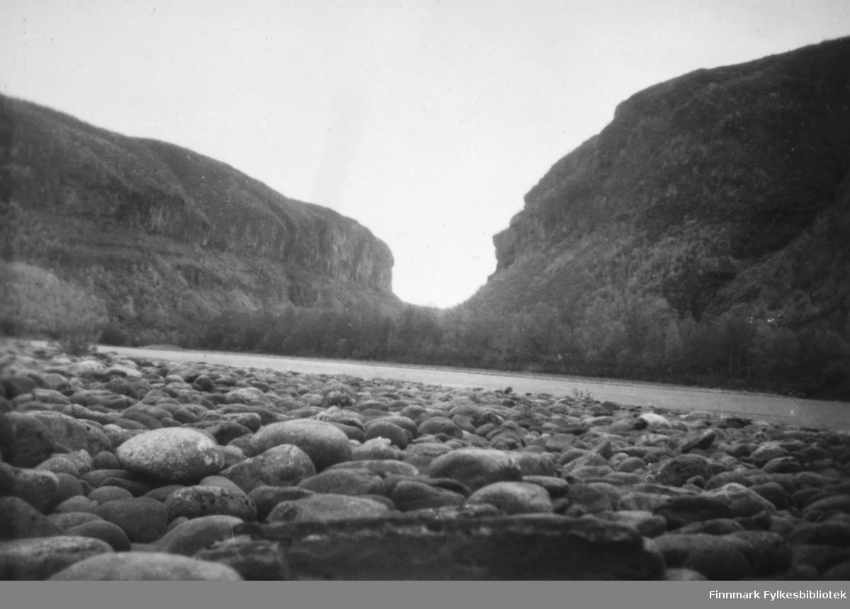 En canyon i Altadalen ses fra Altaelvas bredd. I forgrunnen ser vi en rullesteinstrand. Langs elva ser vi skog. ca.1950-60.