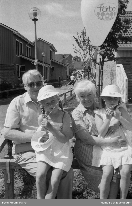 """Firande av Kyrkängens dag i Lindome, år 1985. """"Gammal och ung trivs tillsammans. Johan Wennberg och Kim Westholm i knäet på Viola och Harry Dovervång.""""  För mer information om bilden se under tilläggsinformation."""