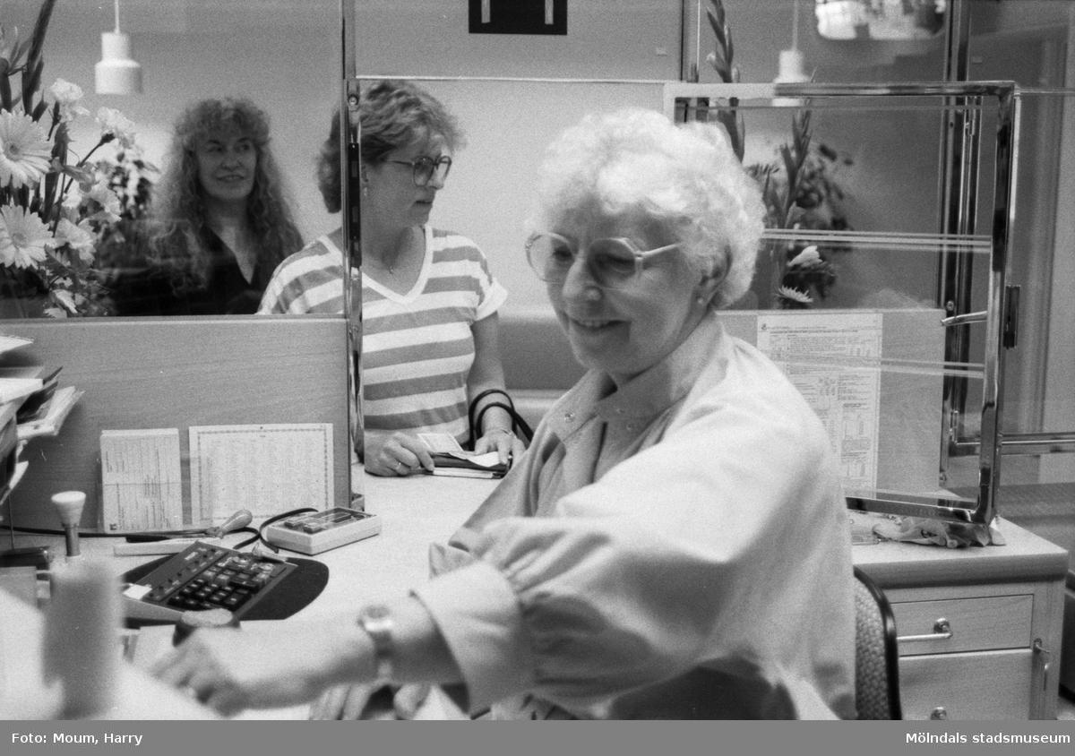 """Nyrenoverade postkontoret på Jungfruplatsen i Mölndal, år 1985. """"Nyöppnat och redan full rulle. Inger Göthage, enligt egen utsago fast inventarium på Jungfruplatsens postkontor, fixar utbetalningar till Saija Wäisänen i luckan.""""  För mer information om bilden se under tilläggsinformation."""
