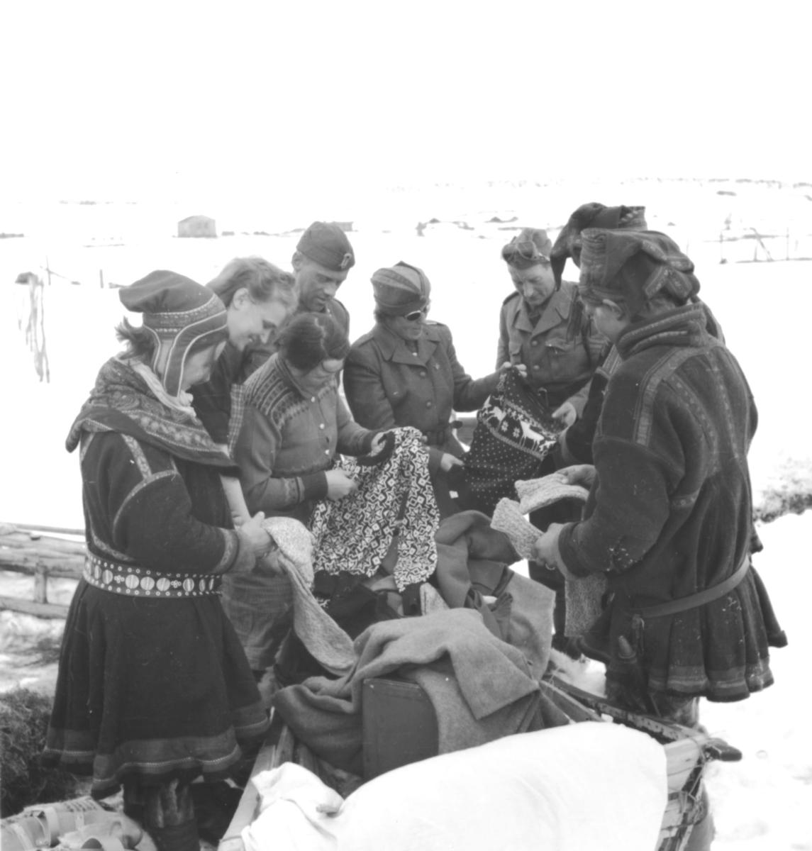 Samer og politisoldater står over en eske med klær og ulltepper. Dette er fra Kautokeino eller Lakselv.