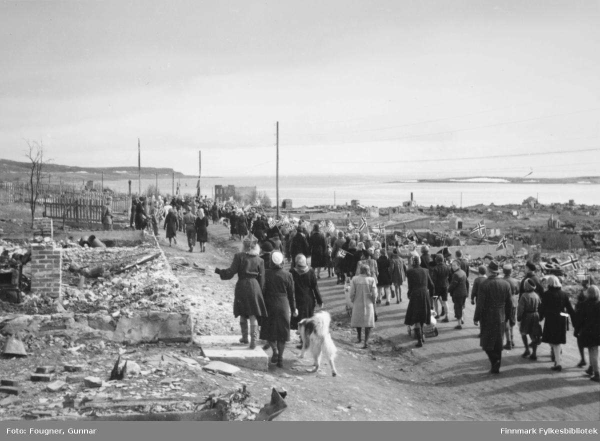 8.mai 1945 i Vadsø. En gruppe barn og voksne går i tog.