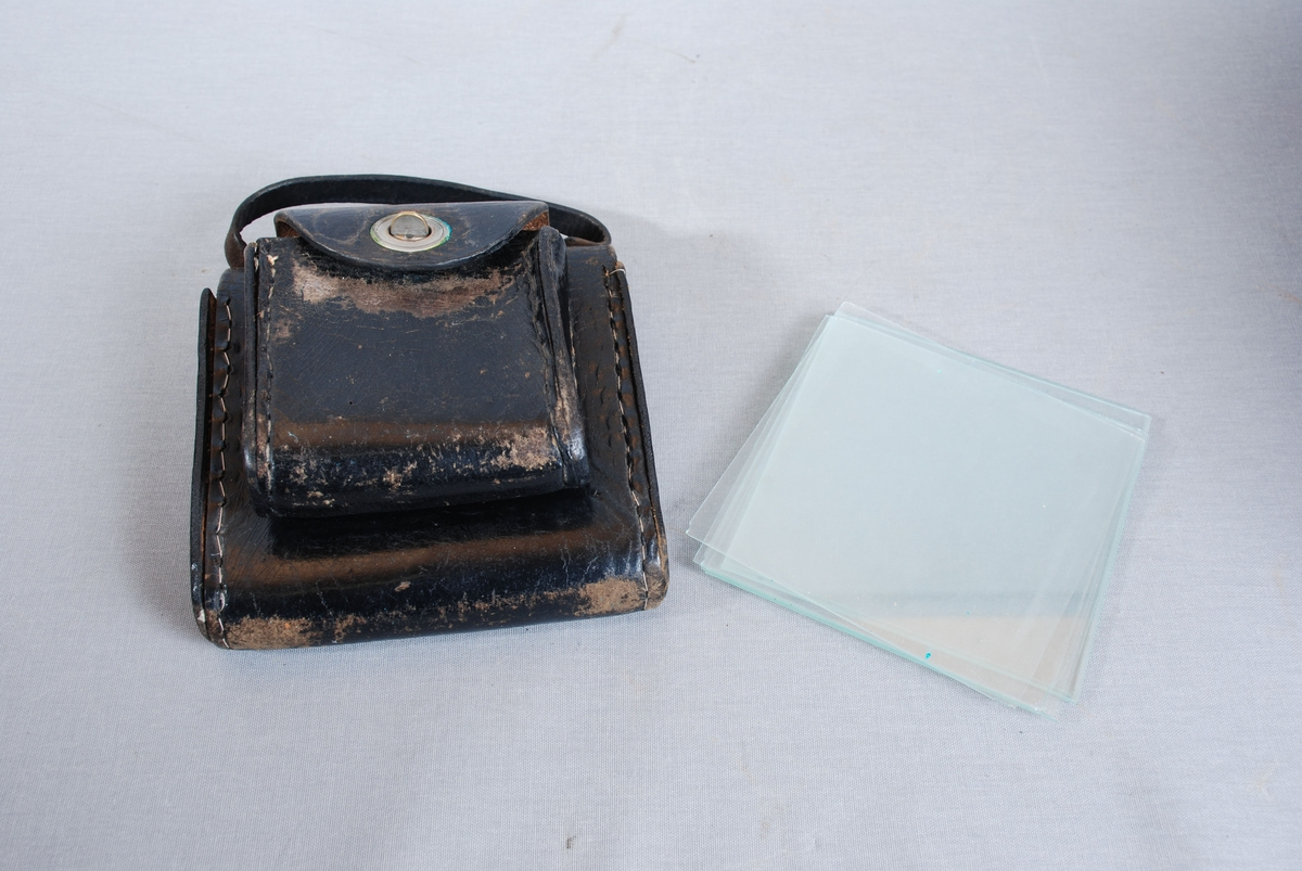 Dobbel veske med glassplater til brannmeldere der glasset er knust. Vesken er rektangulær med klaffelokk og lukking med vridbare metalknapper. De to delene har ulik størrelse, og henger fast i hverandre rygg mot rygg. Lærreim festet i toppen av den største vesken. Inne den minste lommen 41 stk papirlapper, hvorav den ene er revet istykker. I den største beholderen er det 14 stk glassplater i to ulike størrelser.