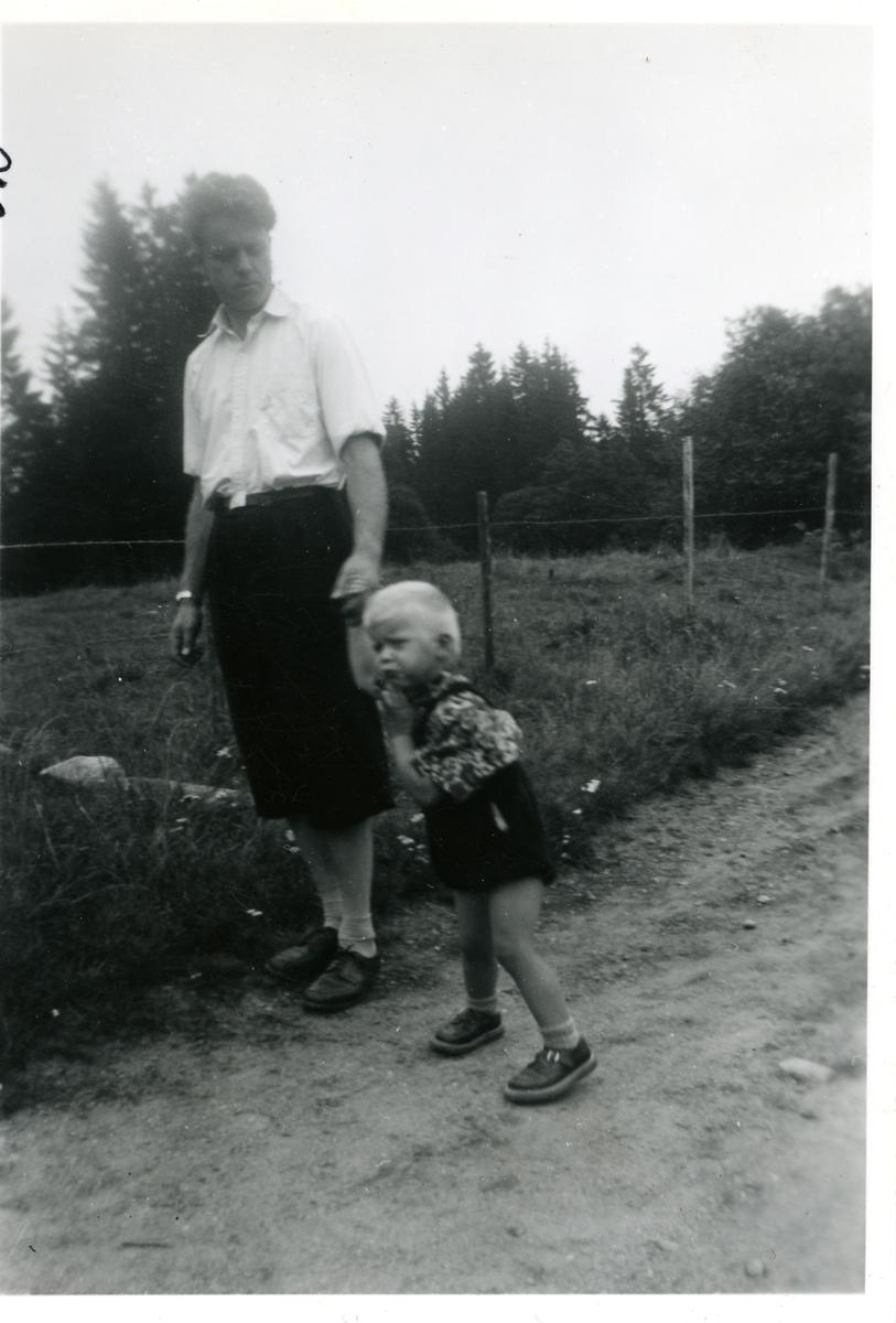 Mann og barn stående på en grusvei, ved siden av et gjerde