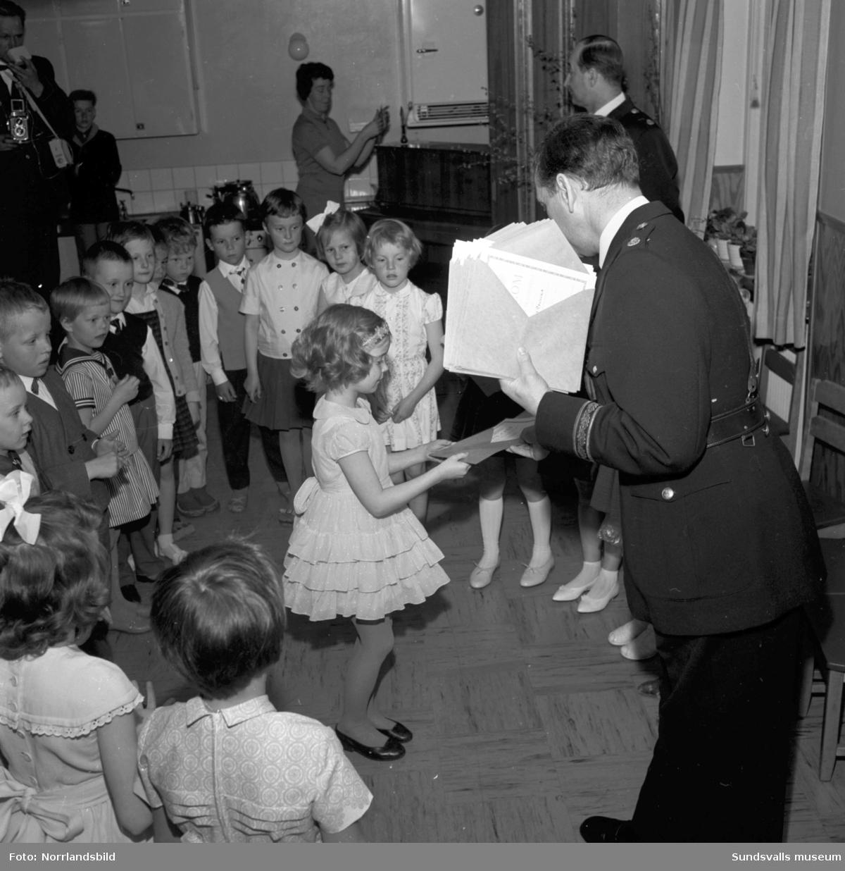 Polismästaren delar ut diplom på lekskolorna.