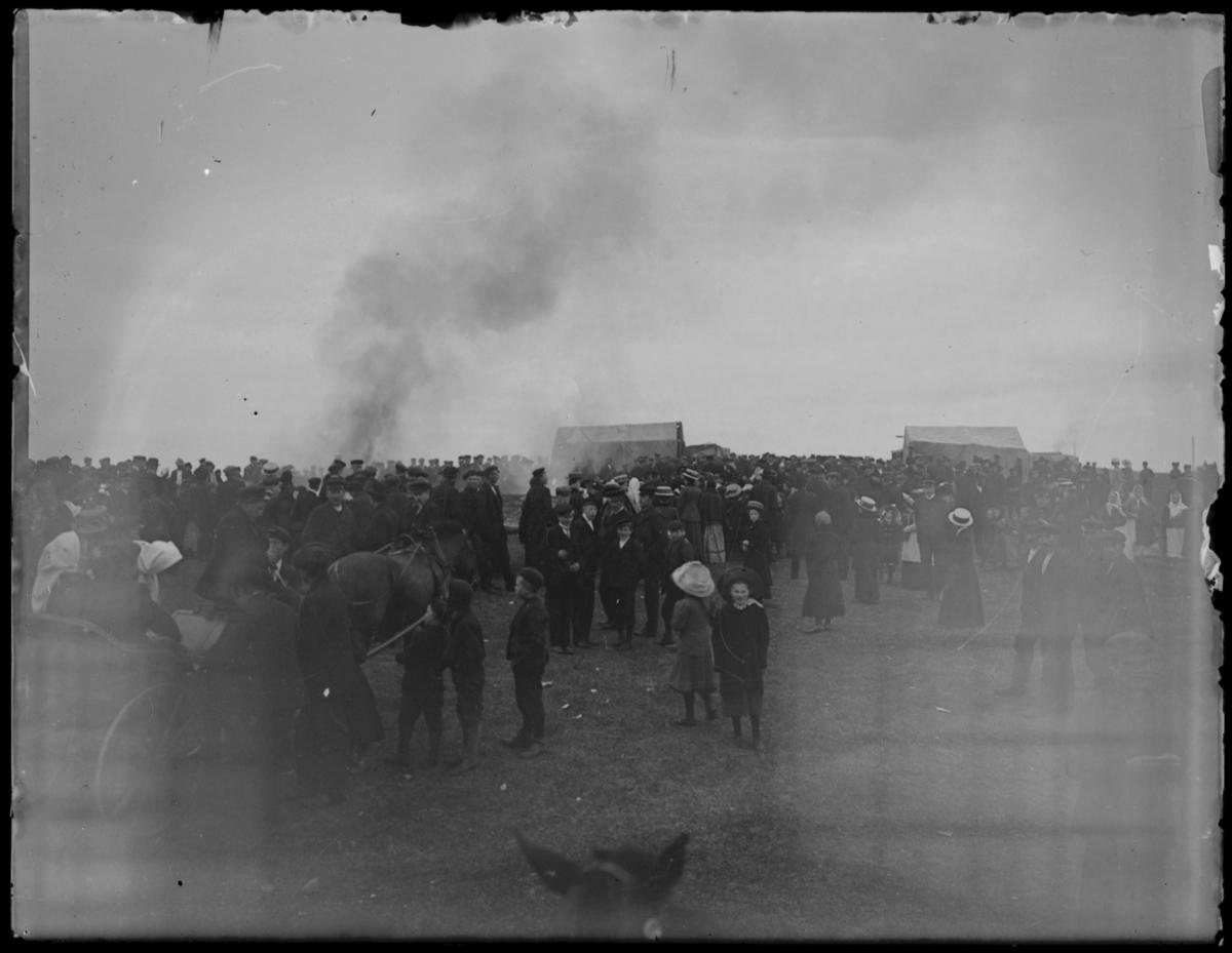 Antakelig St.Hansfeiring på Skagen i Vardø. En stor folkemengde, noen kommer med hestekjerrer. To jenter står midt på bildet i store hatter. Det ryker fra et bål