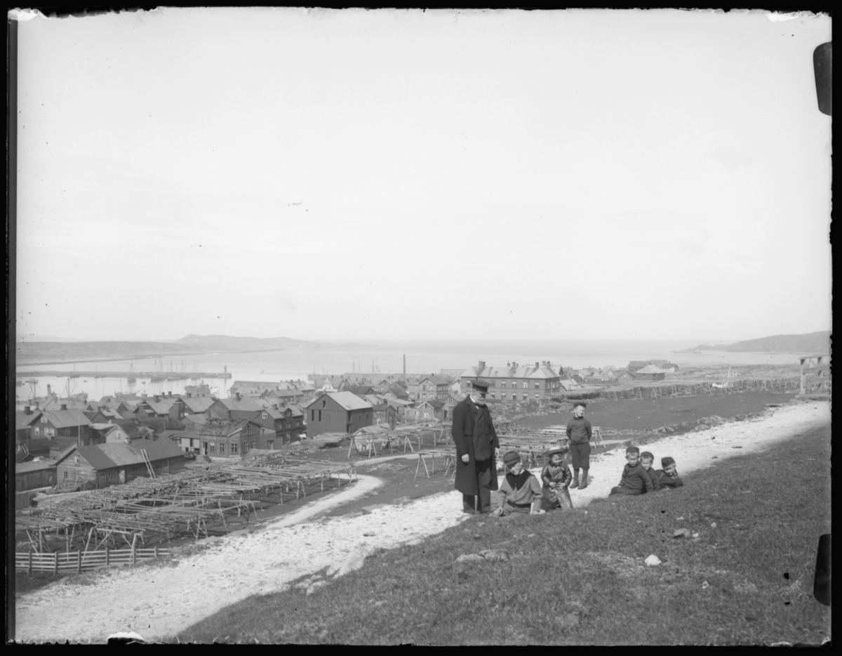 En eldre herre og seks barn, fem gutter og ei jente, på utflukt mot Kirkeberget i Vardø en deilig vårdag med sol. I bakgrunnen ser vi bebyggelsen og moloen på Nordre våg. Den store bygningen litt til høyre på bildet Vardø sykehus