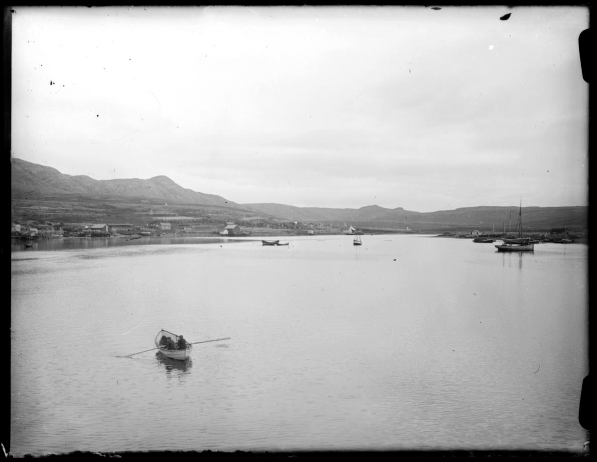 En rolig havn et lite sted langs kysten av Finnmark, antakelig. Landskapet er ganske flatt, og det ser ut til at havna har en enda smulere del litt lenger inn. På land ser vi hus, fiskehjeller og en fyrlykt. Det ligger noen få seilbåter på havna, og en robåt med en enslig mann er på vei utover