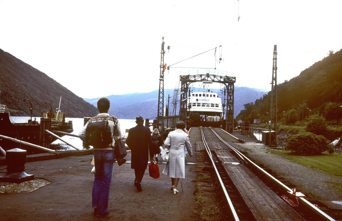 Passasjerer går ombord på jernbanefergen M/F Storegut på Mæl fergeleie, Tinnsjøen. Rjukanbanen. Norsk Hydro, Norsk Transportaktieselskap (Norsk Transport).