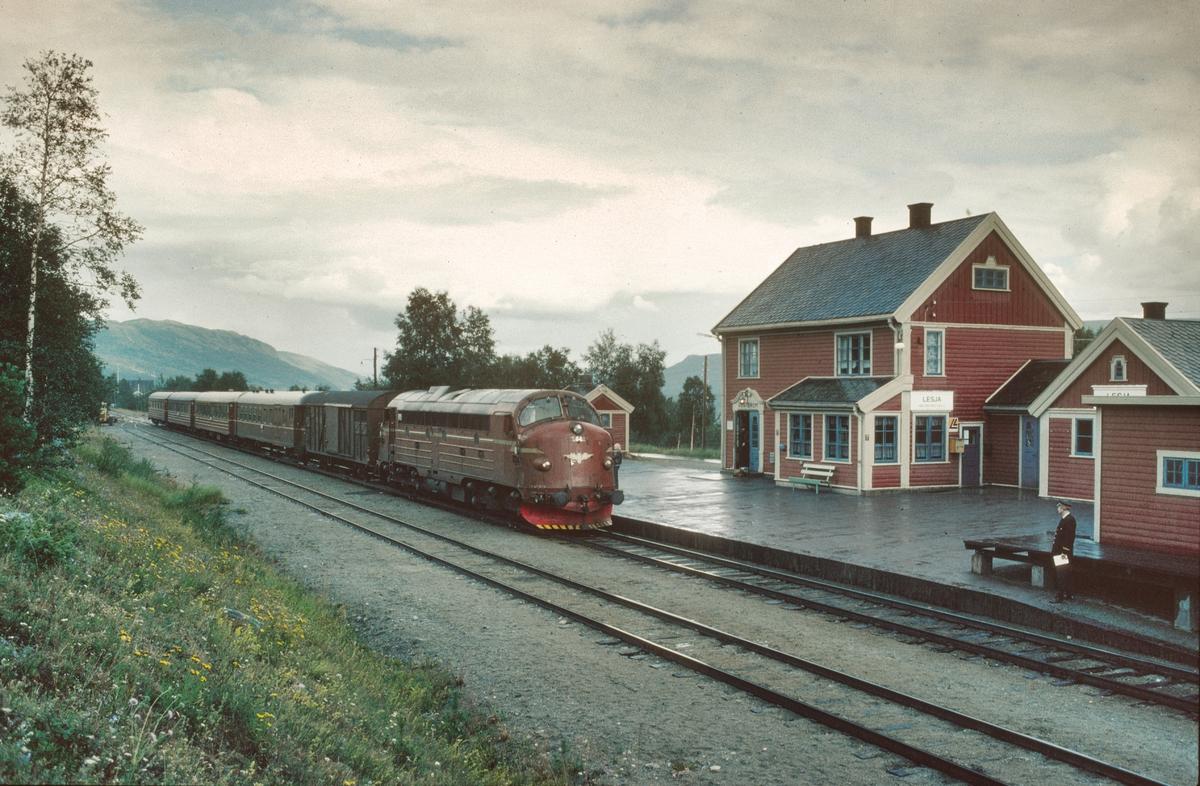 Persontog 351 Oslo Ø - Åndalsnes kjører inn på Lesja stasjon med NSB dieselelektrisk lokomotiv Di 3b 642. Togekspeditøren står klar med telegram til lokomotivføreren.