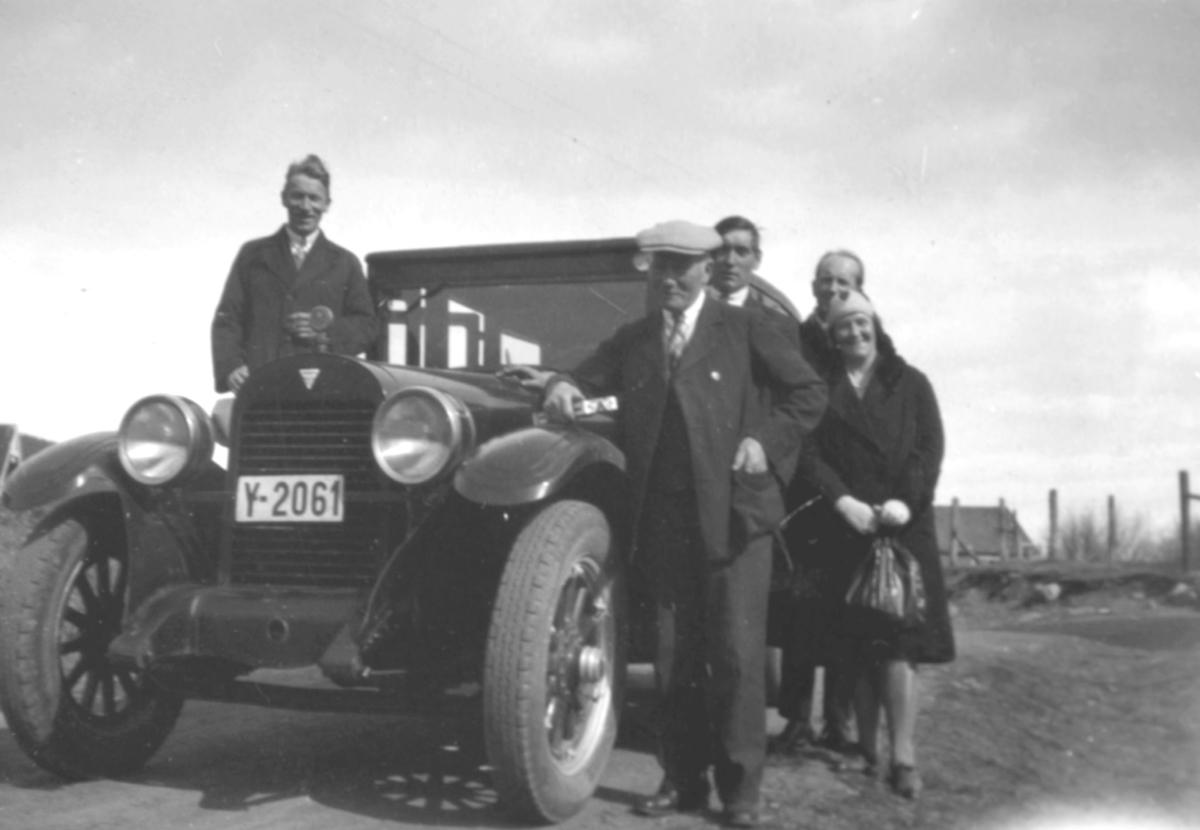 Tre menn og en dame står på høyre side av en bil. På venstre side en mann. Bilen er en Hudson, eldre enn 1926 og gikk som drosje eid av Ole Henriksen i Bonakas i Tana.