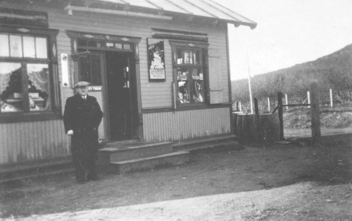En mann står foran trappen til en bygning. Det henger en plakat på venstre høyre siden av døren. Tønner står ved enden av huset.