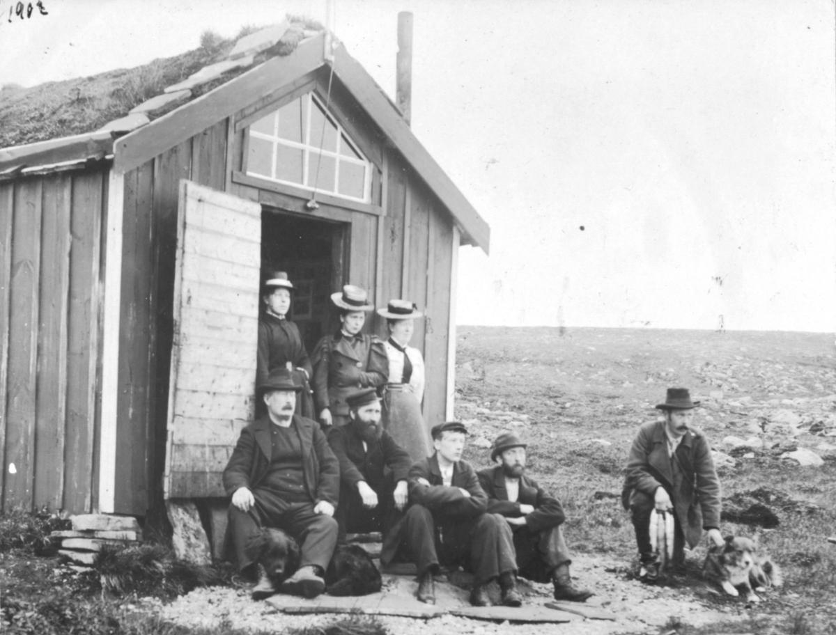 Tre damer står i døråpningen til en hytte. Fire menn sitter foran . Han til venstre har en hund mellom benene. Til høyre sitter en mann med en hund til høyre for seg. I høyre handa ser det ut som om han har 3 fisker. Det er torv på taket til hytta. Over døre ar det et vindu.