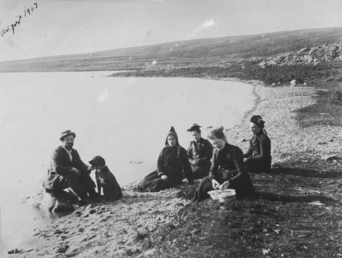 To damer og to menn sitter i fjæra. En mann sitter på en stein i vannkanten men en hund ved siden av seg. Damen forrest er Karoline Ohlsen. Hun sitter med en bøtte og et kar foran seg.