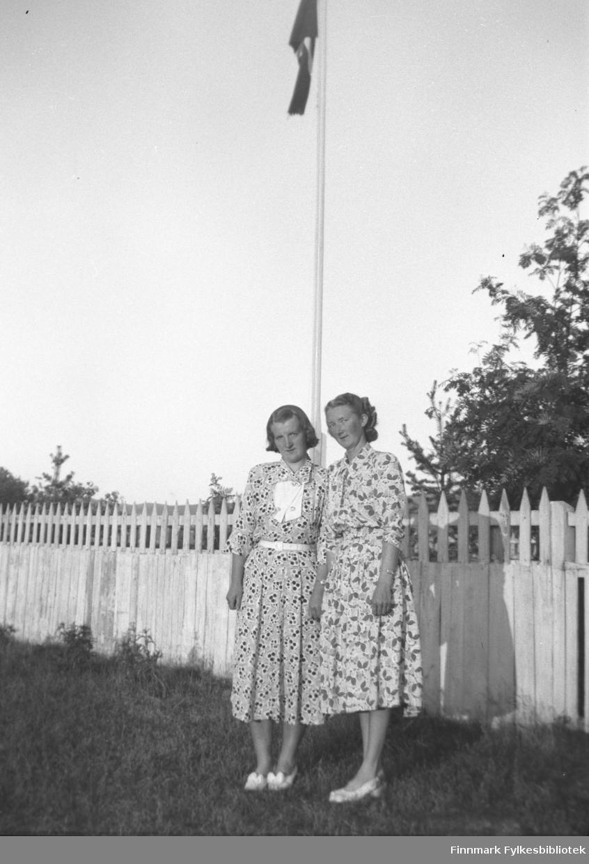 Søstrene Astrid og Marine Mikkola foran flaggstanga på gården Mikkelsnes
