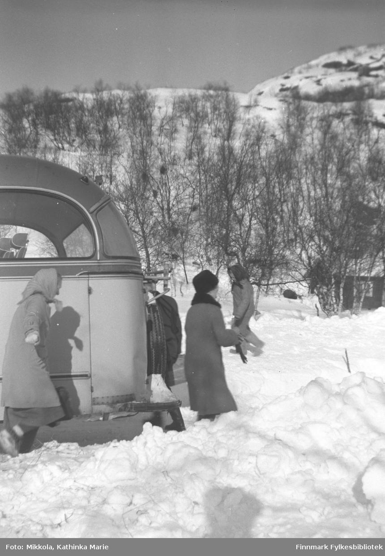 Buss med passasjerer som kommer og går parkert i snøen på Mikkelsnes. Marine Smuk helt til venstre i bildet