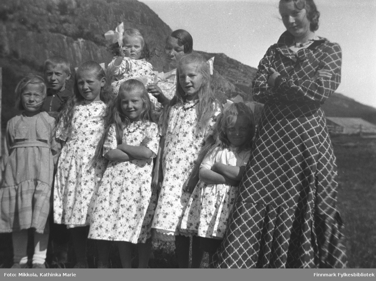 Mange medlemmer av familien Mikkola samlet til fotografering på Mikkelsnes. Bak fra venstre: Åge Mikkola, Herlaug Mikkola på armen til sin tante Inga Mikkola. Foran fra venstre: Elna, Kari, Ingrid, Gudrun, Astrid og Marine Mikkola. Bildet er tatt ved samme anledning som 05007-141
