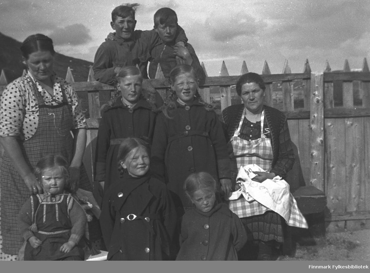 Gruppebilde tatt i hagen på Mikkelsnes, ca. 1924. Foran fra venstre: Herlaug, Kari og Astrid Mikkola. I midten, fra venstre: Kathinka, Gudrun og Ingrid Mikkola, Amanda Olsen Lie med broderi. Guttene øverst, fra venstre: Rubert Olsen Lie og Andreas Mikkola