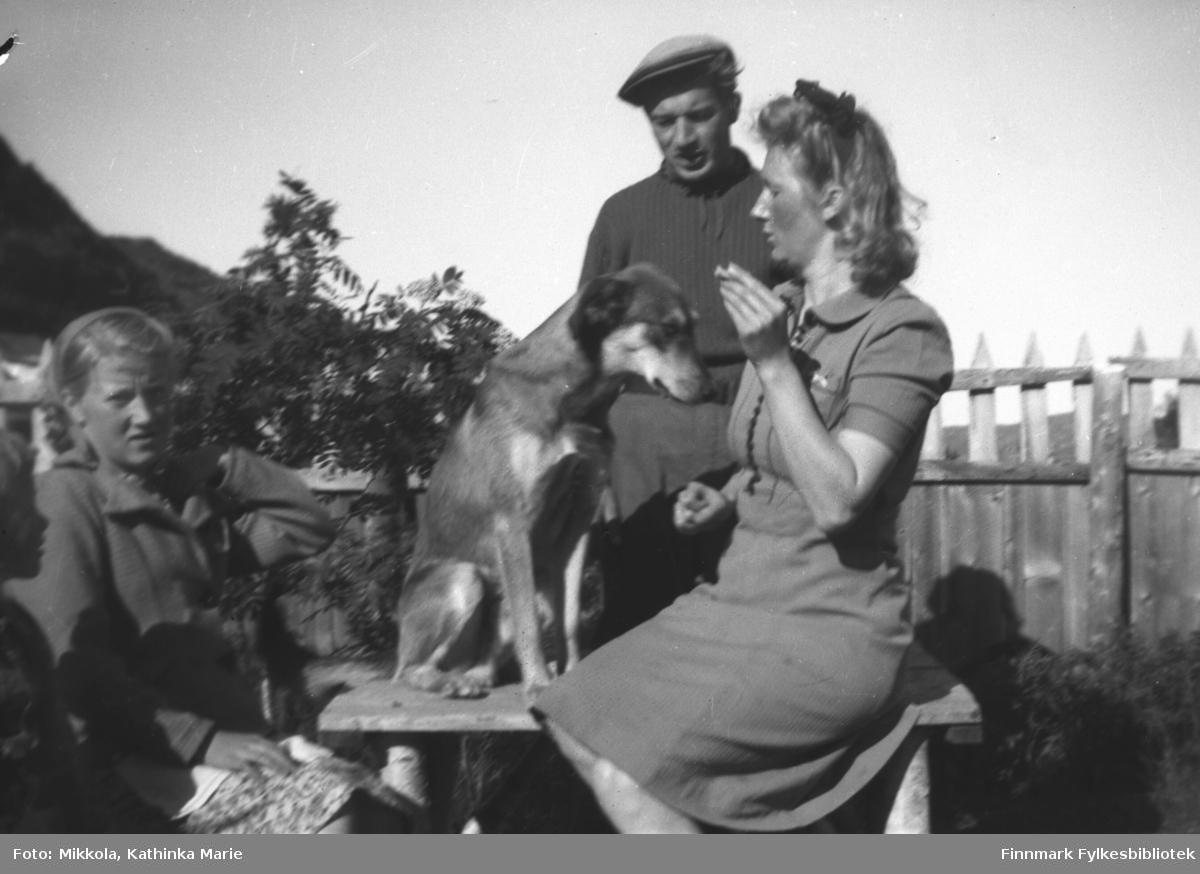 I hagen på Mikkelsnes, ca. 1942. Marine Mikkola med en tiggende hund til høyre. Herlaug Mikkola til venstre, og bak står Andreas Mikkola