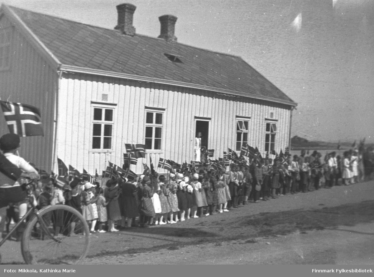 Skolebarn med flagg foran en lys bygning. Bildet kan være tatt en 17. mai, eller i anledning et kongebesøk? Vi vet ikke hvor i landet bildet er tatt