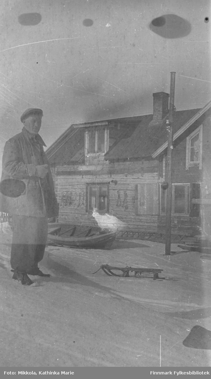 En ung mann i vinterklær (kan være Storm Mikkola) i snøen på Mikkelsnes. Han står ved en liten kjelke. I bakgrunnen et tømmerhus med en robåt trukket opp ved siden av. Det er sperret opp små skinn på husveggen - hareskinn?