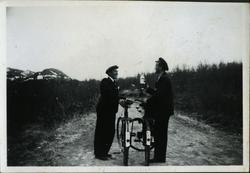 To menn står med hver sin sykkel på en grusvei. Mannen til v