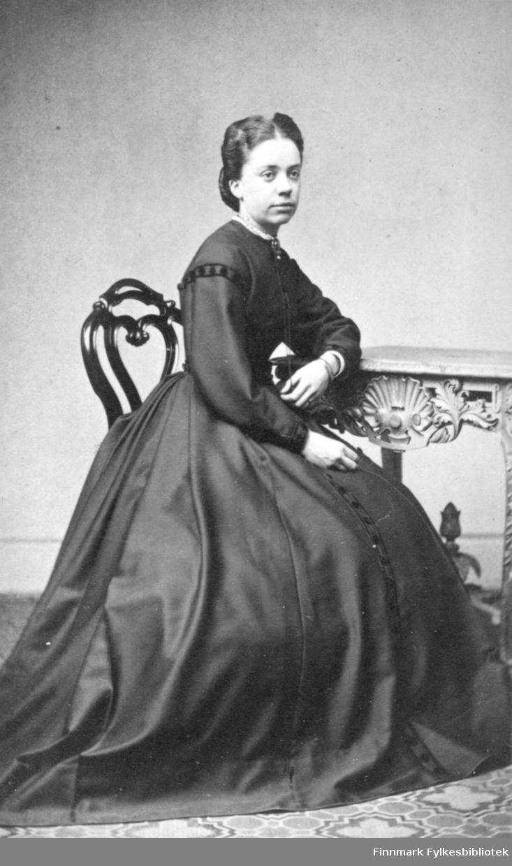 Portrett av en dame som sitter ved et lite bord som hun hviler venstrearmen på. Hun har en stor, lang og mørk kjole på seg. Bordet har utskjæringer langs kantene. Portrettet er tatt av Frederik Klem i Christiania.