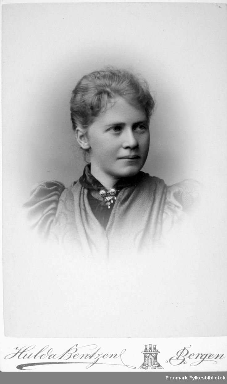 Portrett av en dame med en ganske lys bluse. Hun har et mørkt klesplagg under og en brosje er festet i kragen foran.