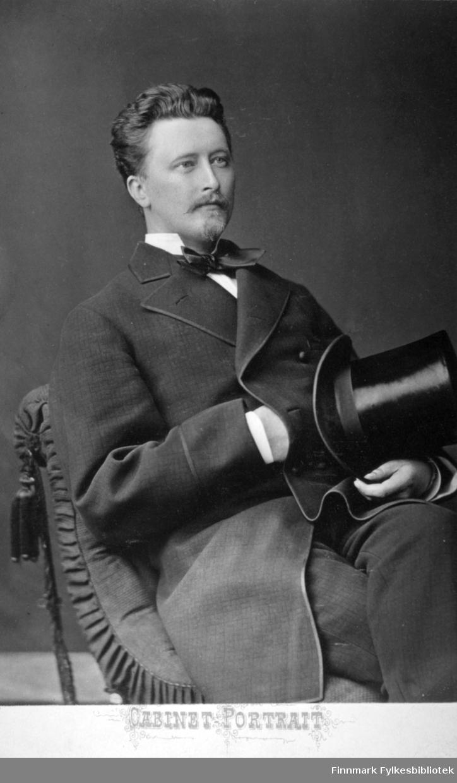 Portrett av en ung mann i en mørk dress, hvit skjorte og sløyfe i halsen. Fotografert hos Behrends Atelier i aug. 1878.