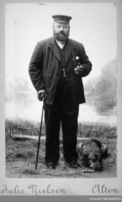 Portrett av en mann med helskjegg. Han er iført mørk dress og skyggelue på hodet. Han har en spaserstokk i høyre hånd og en liten del av en kjede ses hengende over brystet/magen. I halsen vises en liten del av den hvite skjorten han har på seg. En hund ligger på gresset ved føttene hans. Bakgrunnen er et naturmotiv, muligens malt eller en tapet.